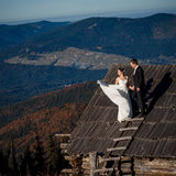 Beautiful wedding couple on the roof of country house. Breathtaking mountain landscape background Stock Image