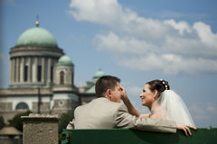Beautiful wedding couple sit on a bench in front of a church. Stock Image