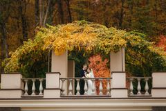 Beautiful wedding couple stand on the balcony. Stylish bride and groom in autumn weather outside.  stock photos