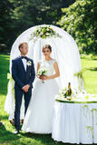 Beautiful wedding couple stands behind a white wedding altar in. The garden Royalty Free Stock Images