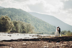 Beautiful wedding couple stay on stone of the river in scenic mountains.  Stock Photo