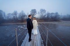 Beautiful wedding couple on the suspension bridge. Misty day in mountains Stock Photos