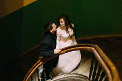 Beautiful wedding couple walk up to stairs smiling each other and holding hands, top view Royalty Free Stock Photos