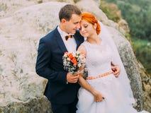 Beautiful wedding couple on wonderful rocky landscape of Carpathians mountains background close up. Stock Photo