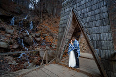 Beautiful wedding couple wrapped in blanket hugs on the wooden bridge. Honeymoon at mountains Royalty Free Stock Photo