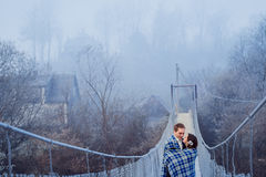 Beautiful wedding couple wrapped in blanket softly hugs on the suspension bridge at mountains. Autumn mountains background Stock Photos
