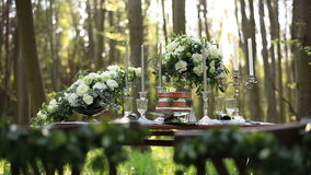 Beautiful wedding decorated table setted for two on nature in the forest. Wedding decoration of white roses bouquets and. Vintage candelabrum near the chocolate stock video