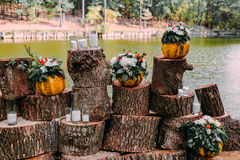 Beautiful wedding decoration autumn wedding in orange colors. An outdoor ceremony near a lake. Pumpkins, flowers, and. Candles. Horizontal Stock Photos