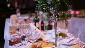 Beautiful wedding decoration made of flowers of different kinds and colors on a wedding table in a fancy restaurant. stock footage