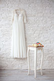 Beautiful wedding dress on hanger white brick wall Stock Image