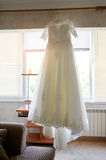 Beautiful wedding dress hanging in the bride's room stock photography