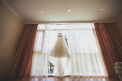 Beautiful wedding dress hanging in the bride`s room Stock Images
