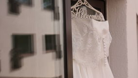 Beautiful wedding dress hanging in a window. stock video footage