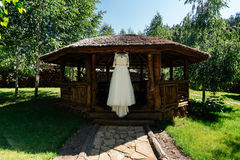 Beautiful wedding dress hanging on the wooden arbor. Next to the birch outdoors royalty free stock photos