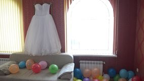 Beautiful wedding dress in the room with colorful balloons. stock video