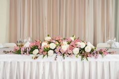 Beautiful wedding floral decoration on a table in a restaurant.White tablecloths, bright room. stock image