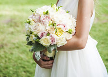 Beautiful wedding flowers in hands. Girl in white dress hold beautiful wedding rose bouquet Stock Photography