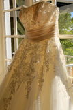 Beautiful wedding gown hanging in window Royalty Free Stock Photos