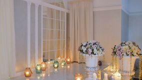 Interior of wedding hall. Beautiful wedding hall with different decorations. Small burning candles stands on the floor. The bouquets of flowers are in the vases stock video footage