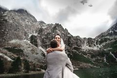 Beautiful wedding photosession. The groom circles his young bride, on the shore of the lake Morskie Oko. Poland stock images