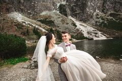 Beautiful wedding photosession. The groom circles his young bride, on the shore of the lake Morskie Oko. Poland royalty free stock images