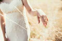 Beautiful wedding ring on bride hand touching ear on field in su Stock Photo