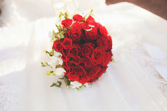 Beautiful wedding rings and a bouquet of red roses.  Stock Image