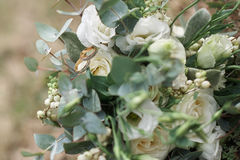 Beautiful wedding rings on a bouquet of white roses Stock Images