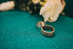 Beautiful wedding rings lie on a wooden surface against the background of a bouquet of flowers. And blue Royalty Free Stock Image