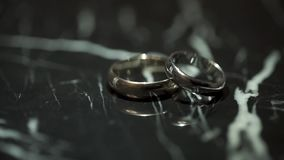Beautiful Wedding rings reflected on a black glossy background. Gorgeous jewelry and flash light. Ring with diamonds on. Black background HD stock footage