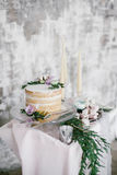 Beautiful wedding round cake with floral decorations and candles. Stock Photography