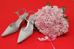 Beautiful wedding shoes and flower. On red background Royalty Free Stock Photo