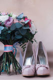 Beautiful wedding shoes with high heels and a bouquet of colorful flowers Stock Photos