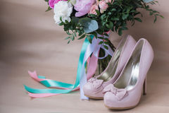 Beautiful wedding shoes with high heels and a bouquet of colorful flowers Royalty Free Stock Photos
