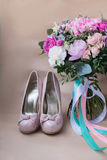Beautiful wedding shoes with high heels and a bouquet of colorful flowers Stock Photo