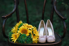 Beautiful wedding shoes with high heels and a bouquet of sunflowers on a vintage chair Stock Image
