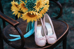 Beautiful wedding shoes with high heels and a bouquet of sunflowers on a vintage chair Stock Photos