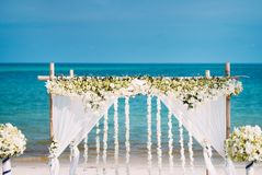 Beautiful wedding arch decoration with flower for wedding venue with panoramic ocean view. The beautiful wedding venue setting with white and green flowers Royalty Free Stock Photos