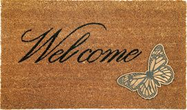 Beautiful welcome peach color coir doormat with Butterfly. Isolated on a White Background stock photos