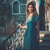 Beautiful well-dressed woman posing on a bridge over the canal in Venice. Royalty Free Stock Photo
