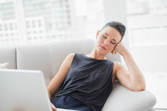 Beautiful well dressed woman resting on sofa while using laptop Stock Images