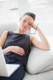 Beautiful well dressed woman resting on sofa while using laptop Stock Image
