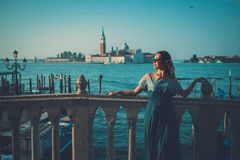 Beautiful well-dressed woman standing near San Marco square with gondolas and Santa Lucia island on the background. Stock Photo