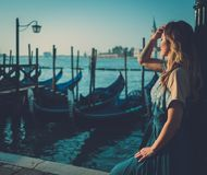 Beautiful well-dressed woman standing near San Marco square with gondolas and Santa Lucia island on the background. Royalty Free Stock Photography
