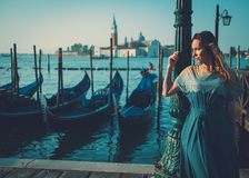 Beautiful well-dressed woman standing near San Marco square with gondolas and Santa Lucia island on the background. Royalty Free Stock Photo