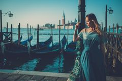 Beautiful well-dressed woman standing near San Marco square with gondolas and Santa Lucia island on the background. Royalty Free Stock Image