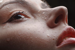 Beautiful wet female face with raindrops on it. Red lips, slightly opened mouth, some water drops on wet face of young girl royalty free stock photography