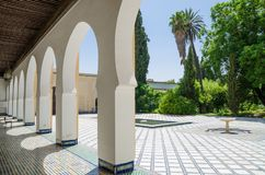 Beautiful white arches of arabic building with lush green garden in Marrakesh, Morocco, North Africa Royalty Free Stock Images