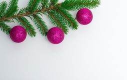A beautiful white background on which lies a branch of a Christmas tree with New Year`s purple balls. Place for text and. A greeting inscription. A beautiful stock photography