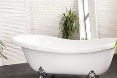 Beautiful white bath in a bright bathroom royalty free stock photos